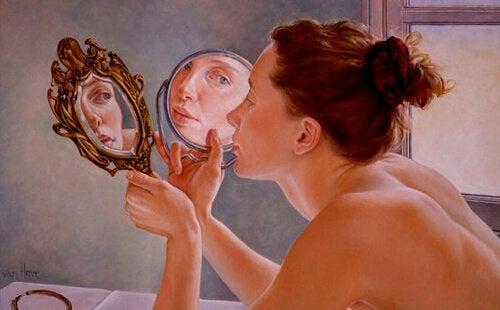 Kobieta patrzy na swoje odbicia w lustrach