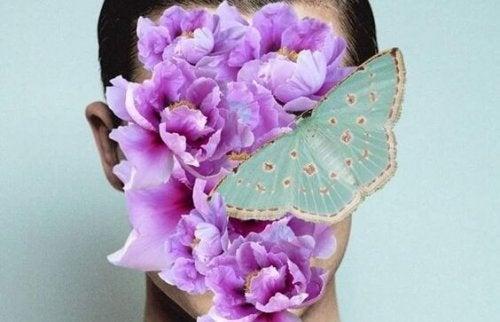 Kobieta z motylem i kwiatami na twarzy.