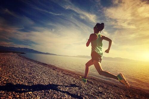Psychologia sportu - kobieta biegnąca po plaży.