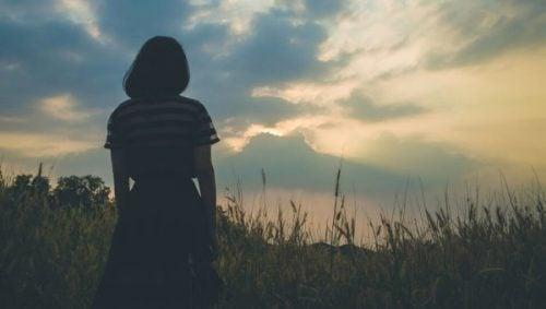 Kobieta patrzy w dal na polu