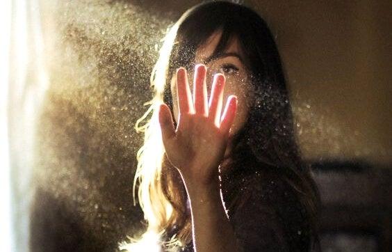 Kobieta dotykająca promieni słonecznych.