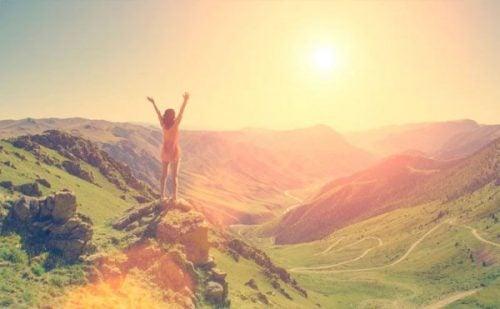 Kobieta triumfuje nad okolicznościami stojąc na górze
