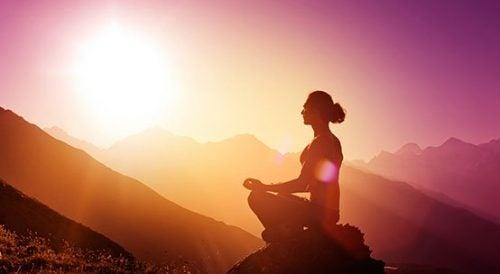Mantry medytacyjne - kobieta medytuje w górach