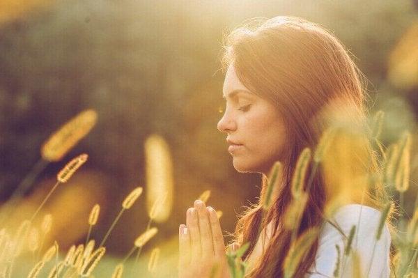 Kobieta medytująca na łące.