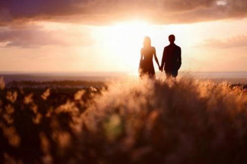 Para trzymająca się za ręce o zachodzie słońca