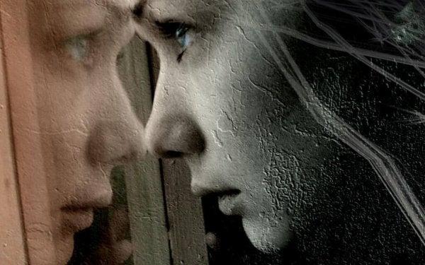 Smutna kobieta patrząca przez szybę.