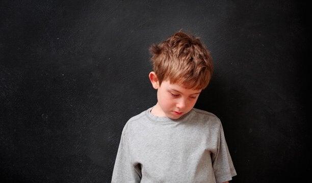 Smutny chłopiec patrzący w dół jako niekochane dziecko