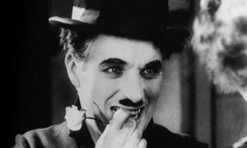 Charles Chaplin uśmiechnięty z kwiatem w dłoni