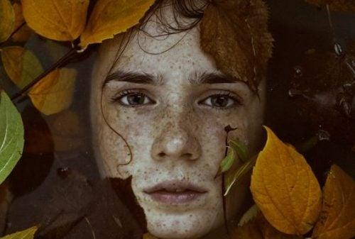 Chłopiec otoczony liśćmi