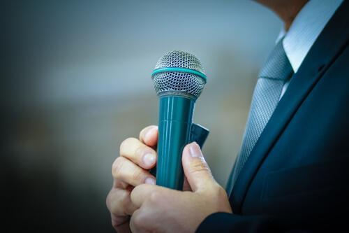 Człowiek trzyma mikrofon - strach przed wystąpieniami publicznymi