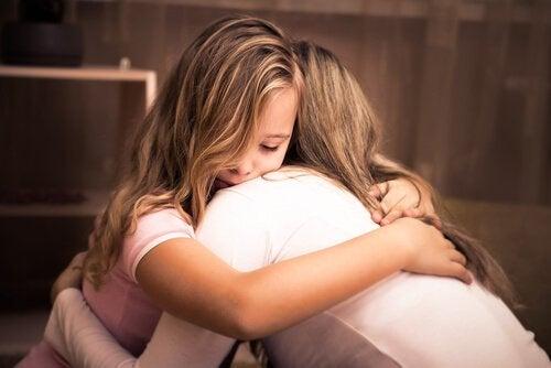 Wsparcie emocjonalne - dziewczynka przytula się do matki.