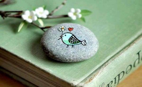 Kolorowy ptaszek namalowany na kamyku.