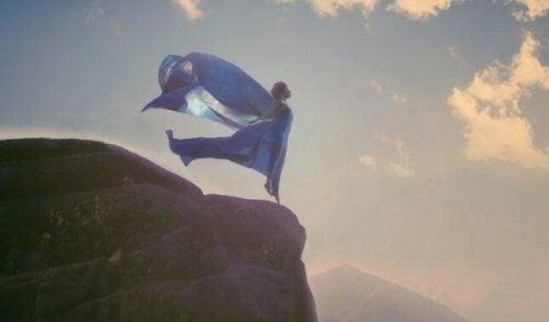 Kobieta stoi na klifie smagana wiatrem