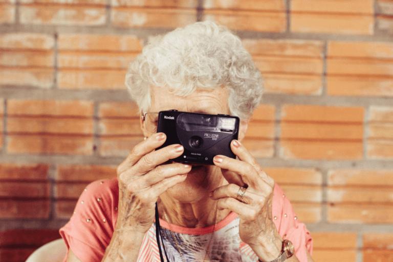 Starsza kobieta z aparatem fotograficznym.