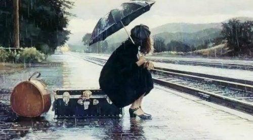 Kobieta z parasolem siedzi na walizce przy torach