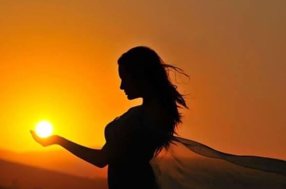 kobieta ze słońcem w dłoni