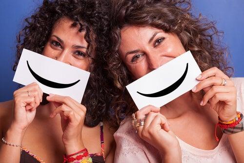 Przyjaciółki trzymające kartki z narysowanym uśmiechem