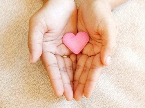 Małe różowe serce w dłoniach