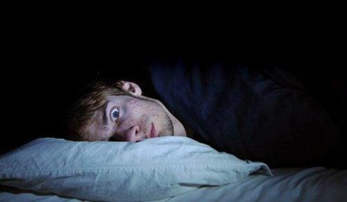 Mężczyzna leży w łóżku z szeroko otwartymi oczami