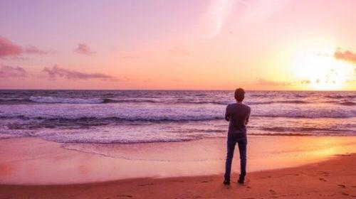 Mężczyzna stoi ze skrzyżowanymi ramionami nad brzegiem morza