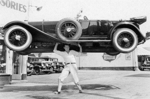 Mężczyzna podnosi samochód