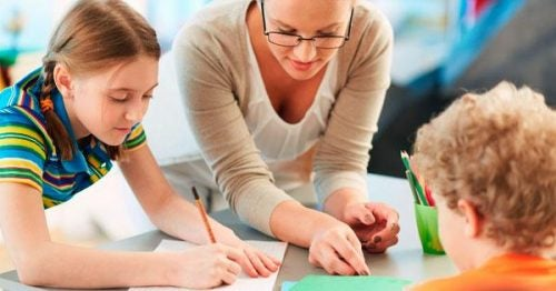 Nauczyciel pomaga dwojgu uczniów