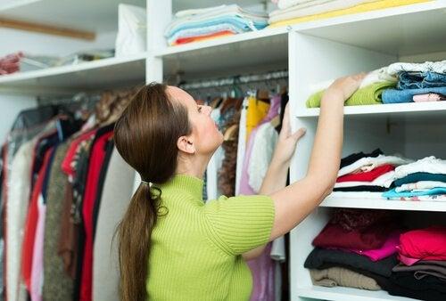 Kobieta układająca ubrania w szafie.