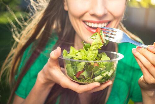 Szczęśliwa kobieta je sałatkę