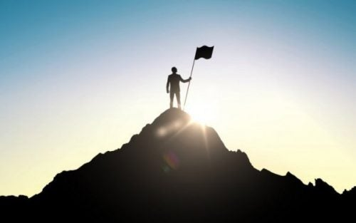 Człowiek z flagą na szczycie góry