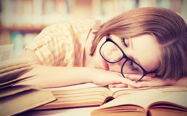 Kobieta śpiąca przy biurku.