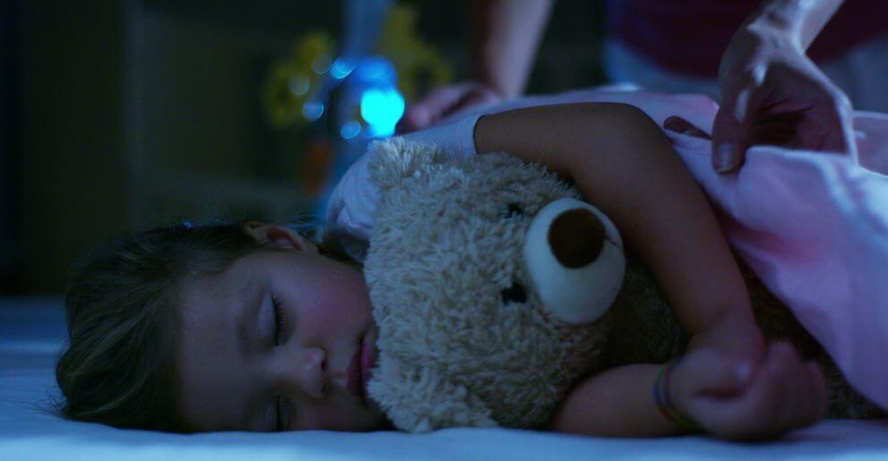 Śpiąca dziewczynka z misiem.