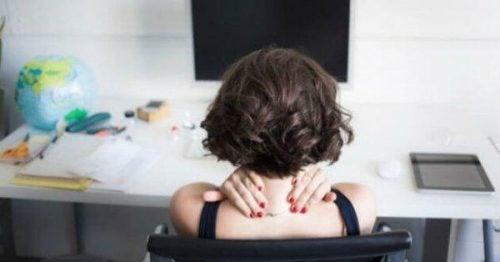Kobieta przy biurku z bólem karku
