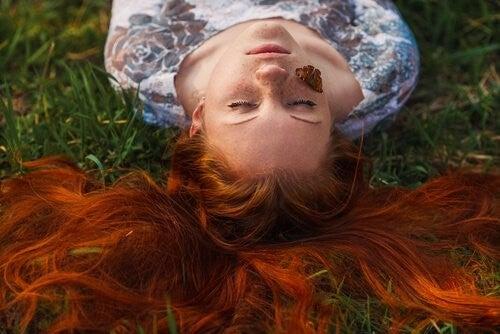 Kobieta z motylem na twarzy.