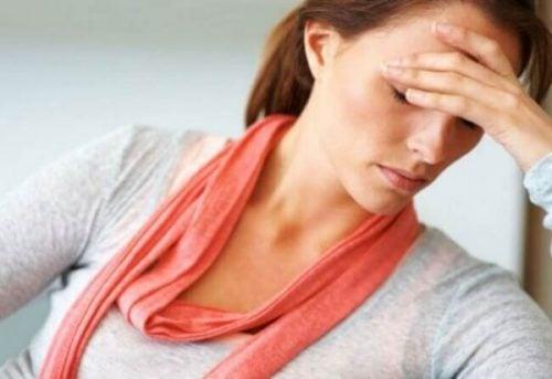 Zmęczona kobieta trzyma się za głowę