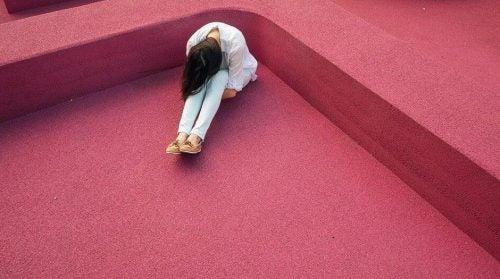 Kobieta w rogu pokoju cierpi na chroniczny ból