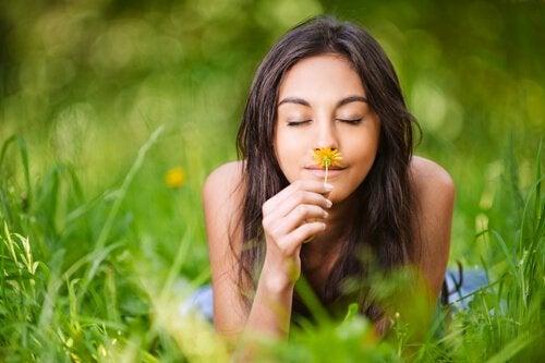 Kobieta wącha kwiatek.