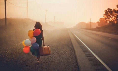 Dziewczyna z kolorowymi balonikami i walizką.
