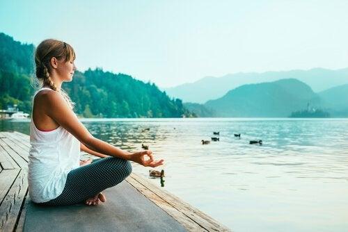 Kobieta medytująca nad jeziorem.
