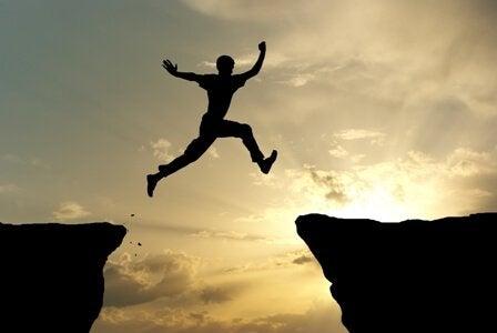 Mężczyzna skaczący nad przepaścią.