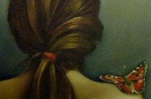 Motyl na nagim ramieniu kobiety