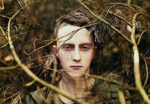 Chłopak między drzewami.