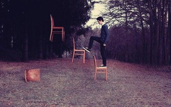 chłopak wchodzący po krzesłach jak schodach