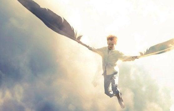 chłopiec z wielkimi piórami jako skrzydła