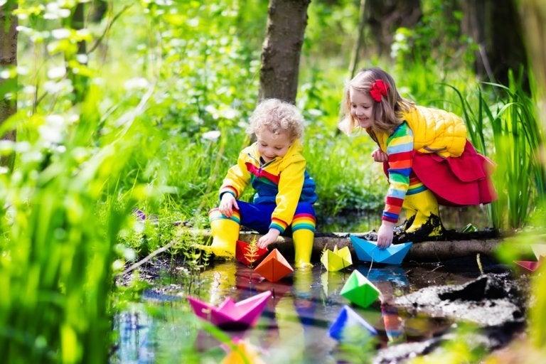 Dzieci puszczają kolorowe statki nad rzeką