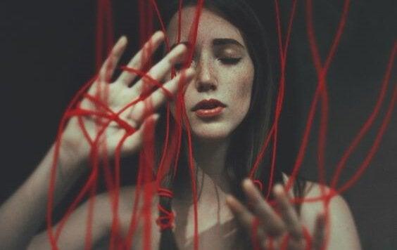 dziewczyna otoczona czerwonymi sznurkami