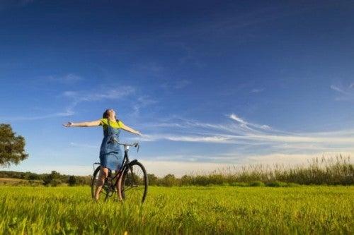 Kobieta siedzi na rowerze na łące