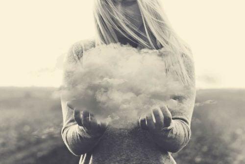 Kobieta trzyma chmurę symbolizującą natrętne myśli