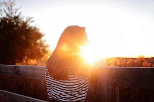 Kobieta patrzy na zachód słońca