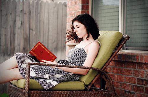 Kobieta czyta książkę na leżaku
