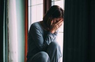 Kobieta płacze siedząc na oknie